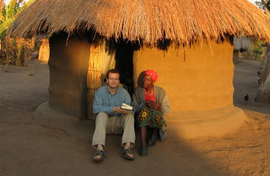 Justin Francis, CEO of Responsible Travel, sits next to a local woman outside her house in Zambia